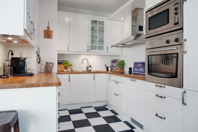 kuchnia w białych na wymiar szafkach i czarno białe płytki na podłodze