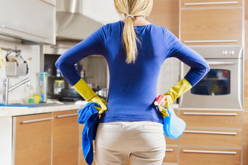 młoda kobieta we wrzosowej bluzce i beżowych spodniach w gumowych żółtych rękawicach stojąca tyłem do na zastanawia się czym wyczyści kuchenne szafki