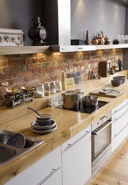 ceglana ściana w postaci opaski idealnie wypełnia przestrzeń między szafkami kuchennymi
