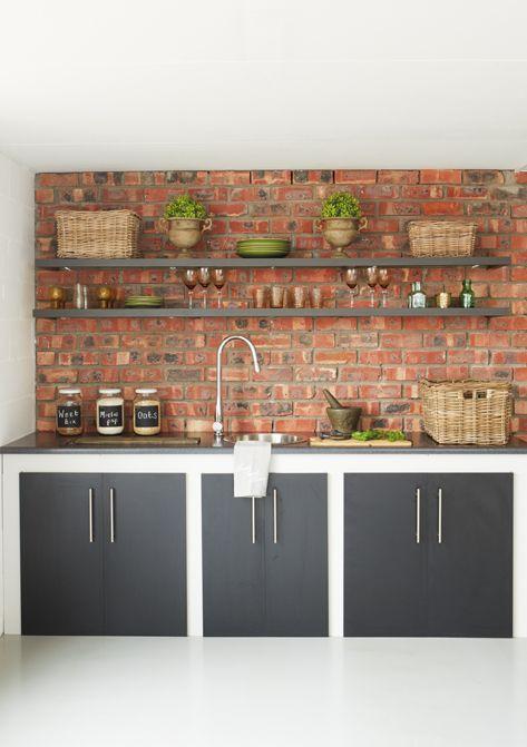 ceglana ściana w kuchni nadaje głębi pomieszczeniu wypełnionym nowoczesną zabudową