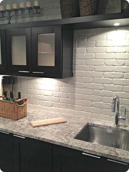 biała ceglana ściana idealnie wypełnia przestrzeń między ciemnymi szafkami kuchennymi