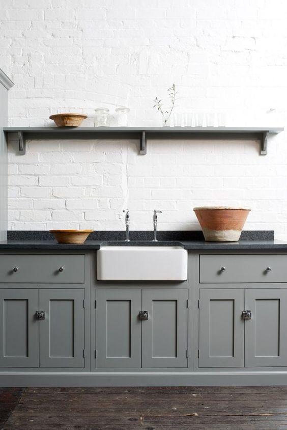 biała ceglana ściana połączona z kuchennymi szafkami w odcieniu szarości z ciemnym blatem