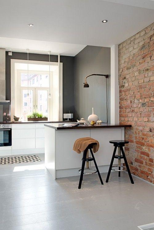 nowoczesny aneks kuchenny idealnie się łączy z ceglaną ścianą sąsiedniego pomieszczenia