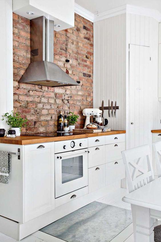 ceglana ściana nadaje ciepła białej kuchni